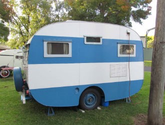 The caravan has the typical rounded shape of a 1950s wooden van, but has been modernised with an alu