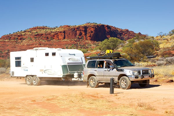 Family on the road driving and towing a caravan