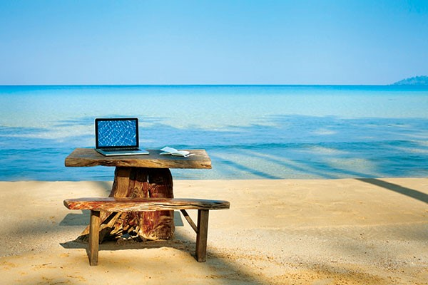 Laptop on a bench at the beach