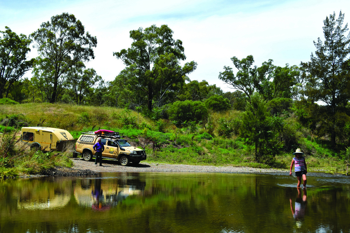 A person is walking across the river ahead of the 4WD