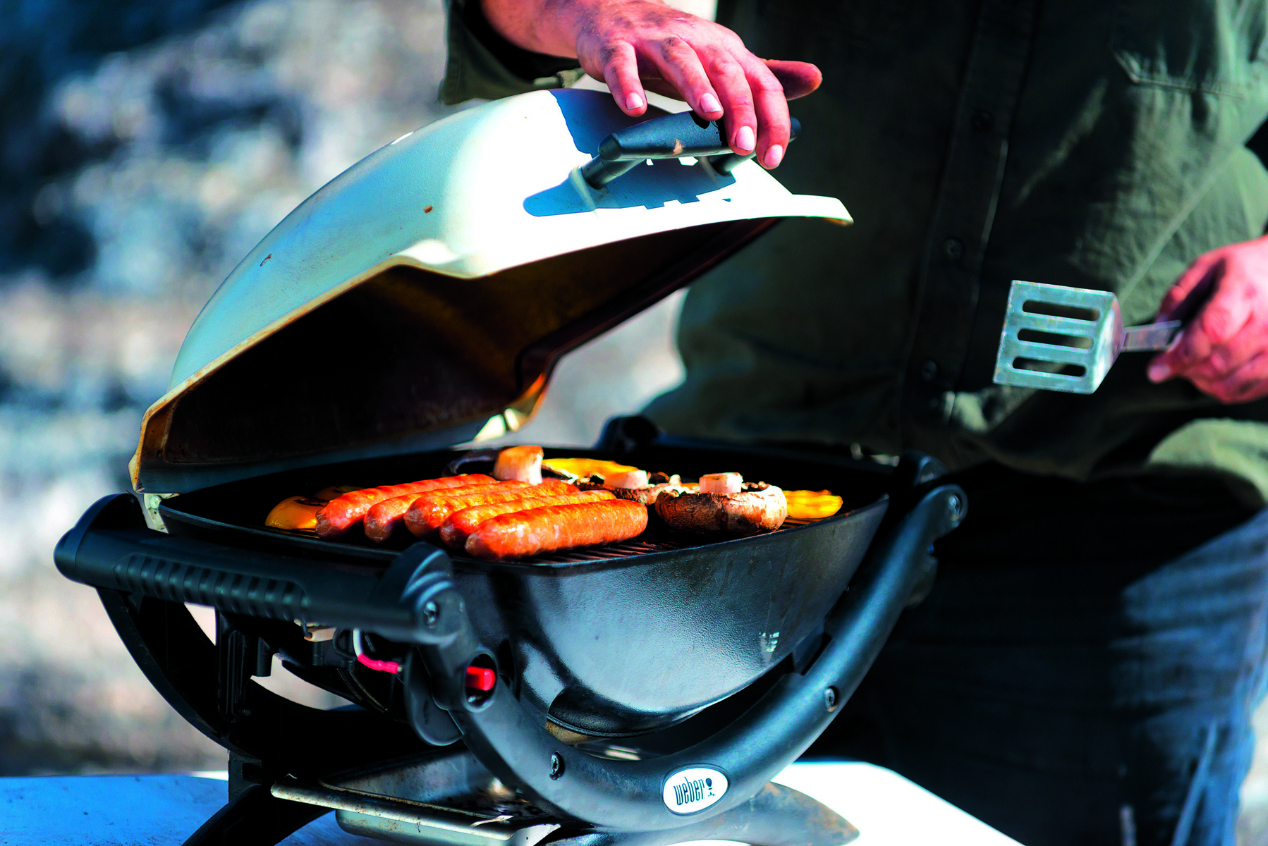 Man cooking on a Weber barbecue