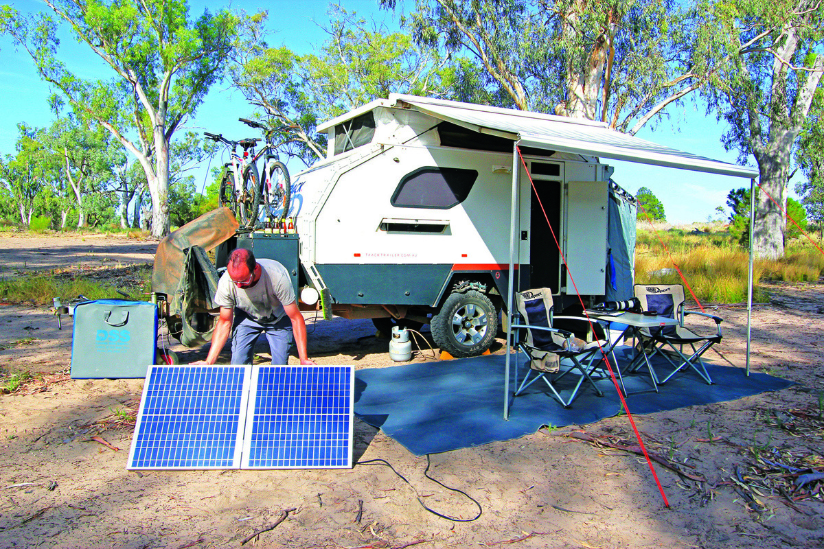 Man holding solar panels outside of caravan