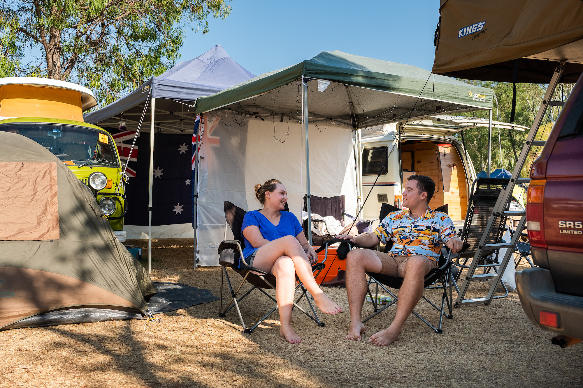 A family sitting around their campsite for the festival