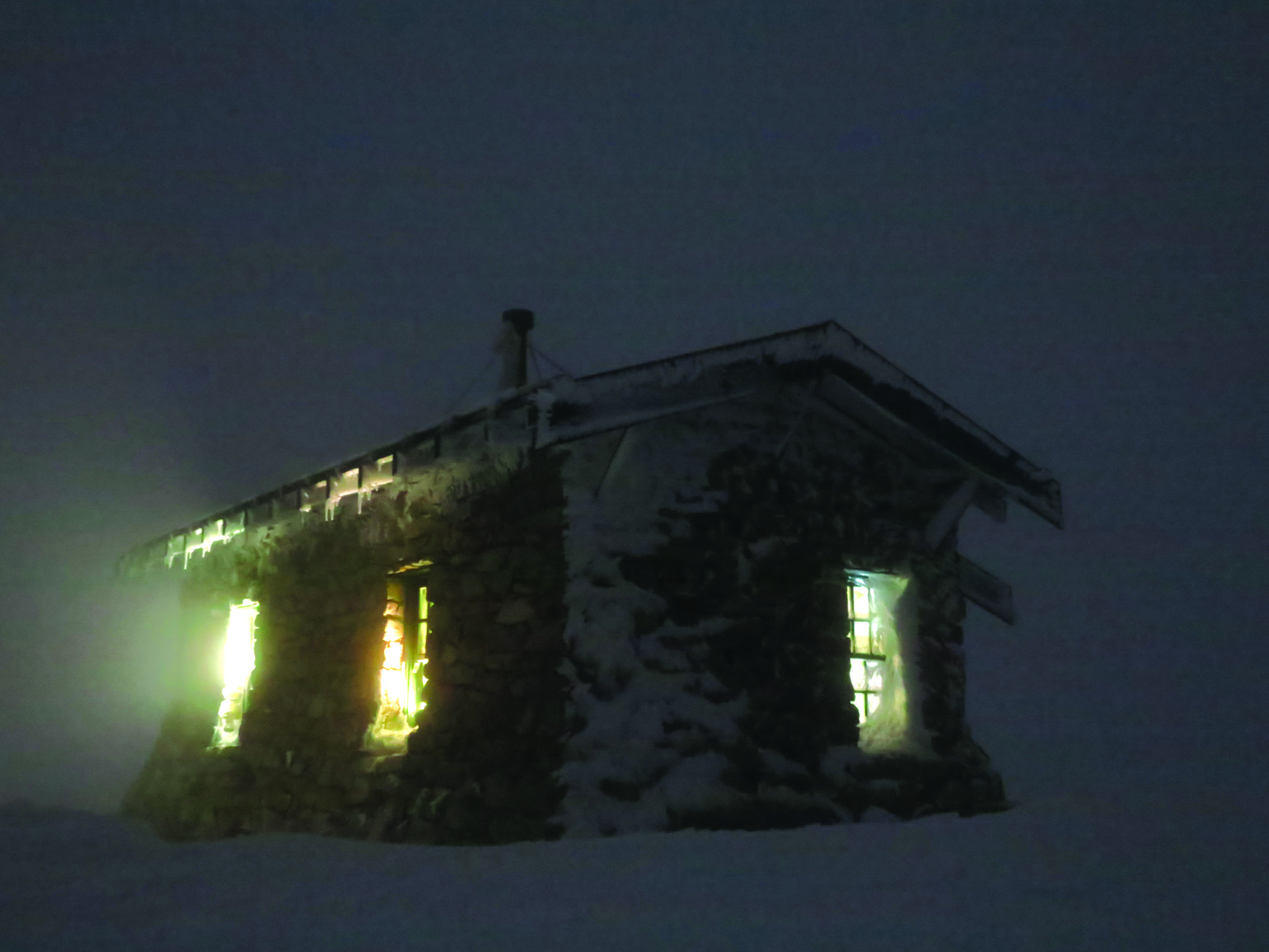 The hut, aglow from inside at night